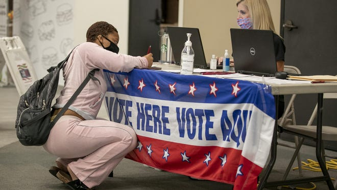 Hays County Elections Administrator Jennifer Anderson, right, helps student Serenity Courtney, 18, register to vote at Texas State University in San Marcos on Tuesday.