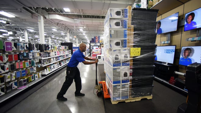 Best Buy inventory associate Kione Mercer stocks sound bars for shoppers at the Poughkeepsie Galleria store on Friday.