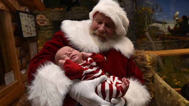 """Five-week-old Leo Daniel Laurent stretches his arms and legs on the warm lap of Santa Claus at the Door County Historical Museum during last year's """"Christmas By the Bay"""" holiday celebration in Sturgeon Bay."""
