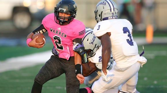 Warren Central quarterback Jordan Leach is pursued by Ben Davis defenders Asmar Bilal, back, and Chris Parish in the first half at Warren Central High School on September 19, 2014. Warren held on to win 28-21.