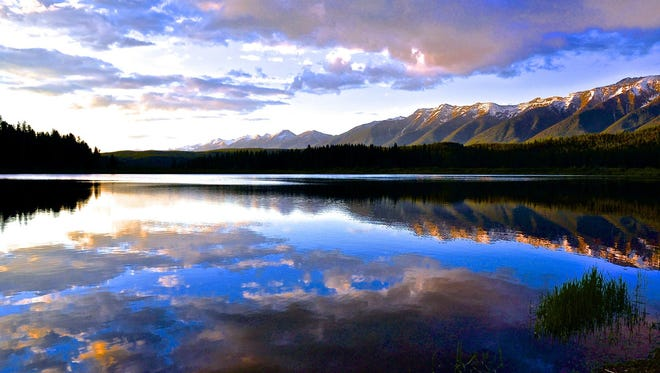 Clouds and mountains reflect off Seeley Lake. The Blackfoot Clearwater Stewardship Project is a conservation, recreation and forest restoration plan for public lands in the Blackfoot and Clearwater valleys.