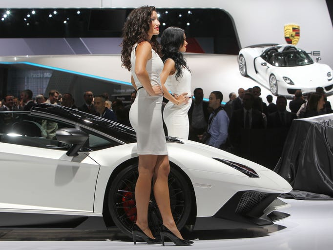 Hostesses pose by a Lamborghini Aventador SV Roadster
