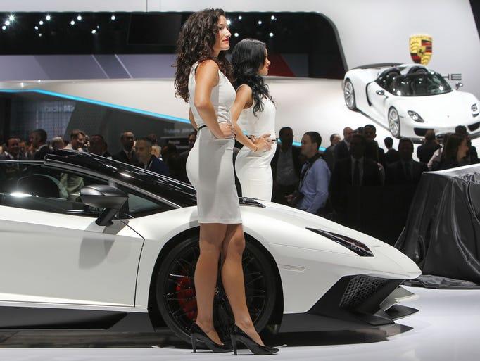 Hostesses pose by a Lamborghini Aventador SV Roadster