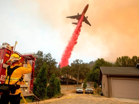 An air tanker drops fire retardant on flames as firefighters continue to battle against the Detwiler fire in Mariposa, California on July 19, 2017.