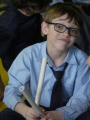 Holy Name third-grader Adam Mitchell with a pair of drum sticks.
