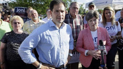 U.S. Sen. Marco Rubio, R-Fla., talks to the media after speaking at a rally for Iowa Republican senatorial candidate Joni Ernst, right, on June 3, 2014, in Urbandale.
