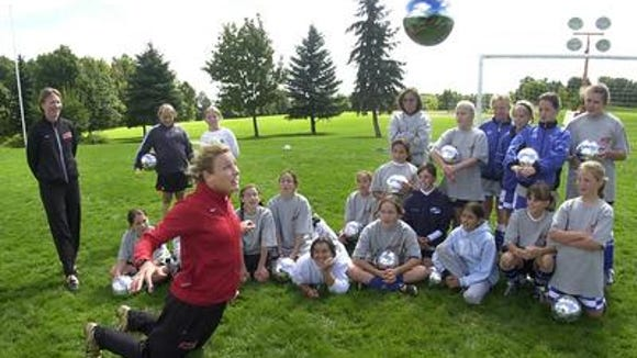 During one of her first local soccer camps in 2004, Abby Wambach shows campers how to properly head a ball.