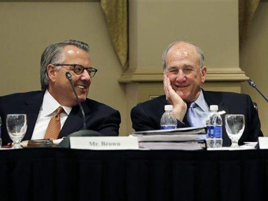 Greg Brown, left, chairman of the Rutgers University board of governors, and Rutgers president Robert Barchi share a laugh before a public meeting in June.