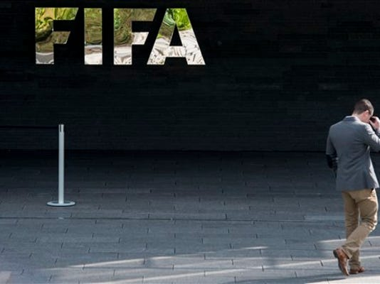 A man walks next to the FIFA logo at the FIFA headquarters in Zurich, Switzerland, Wednesday morning, May 27, 2015.
