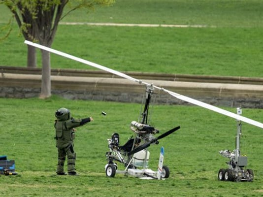 A member of a bomb squad pulls something off of a small helicopter and throws it after a man landed on the West Lawn of the Capitol in Washington, Wednesday, April 15, 2015. Police arrested a man who steered his tiny, one-person helicopter onto the West Lawn of the U.S. Capitol Wednesday, astonishing spring tourists and prompting a temporary lockdown of the Capitol Visitor Center. Capitol Police didn't immediately identify the pilot or comment on his motive, but a Florida postal carrier named Doug Hughes took responsibility for the stunt on a website where he said he was delivering letters to all 535 members of Congress in order to draw attention to campaign finance corruption. (AP Photo/Andrew Harnik)