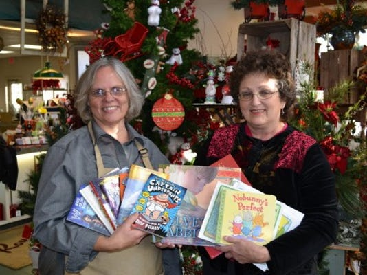 From left, Deb Chrisley, store manager at Royer's West York store; and Karen Hostetter, community relations coordinator with York County Libraries, pose with some of the 1,296 books donated in 2012. The 2013 program runs Nov. 1-9.  (SUBMITTED)