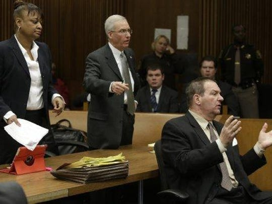 Bob Bashara, convicted in his wife's death, seen here during his sentencing with his defense attorneys, Lillian Diallo and Michael McCarthy. Bashara is seeking a new trial and has blamed his attorneys.