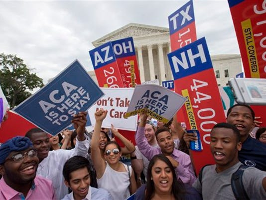 """Students cheer as they hold up signs stating that numbers of people in different states who would lose healthcare coverage, with the words """"lose healthcare"""" now over written with """"still covered"""" stickers, after the Supreme Court decided that the without the Affordable Care Act (ACA) may provide nationwide tax subsidies, Thursday June 25, 2015, outside of the Supreme Court in Washington."""