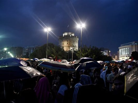 Demonstrators use umbrellas to protect from the rain during a rally organized by supporters of the No vote in the northern Greek port city of Thessaloniki, Friday, July 3, 2015. A new opinion poll shows a dead heat in Greece's referendum campaign with just two days to go before Sunday's vote on whether Greeks should accept more austerity in return for bailout loans.