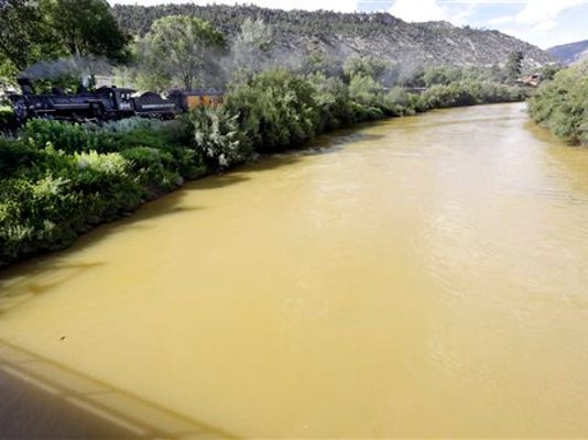 The Animas River is still flowing with toxic waste from the Gold King Mine on Saturday, Aug. 8, 2015, as seen from the 32nd Street Bridge in Durango, Colo., as the Durango & Silverton Narrow Gauge Railroad train goes by.