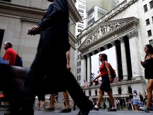 In this Monday, Aug. 24, 2015, photo, pedestrians walk past the New York Stock Exchange.