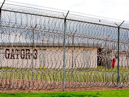FILE - This April 22, 2009, file photo, shows a prisoner, far right, seen behind layers of wire razor fencing at the Louisiana State Penitentiary at Angola, La.