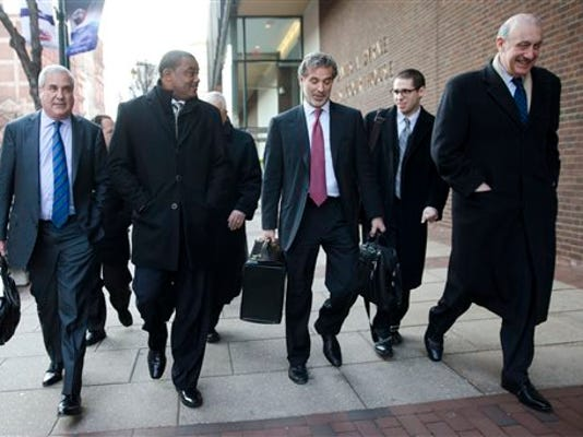 FILE - In this Nov. 19, 2014, file photo, co-lead players' lawyer Christopher Seeger, center right, and client former NFL player Shawn Wooden, center left, speak with members of the media after a hearing on the proposed NFL concussion settlement outside of the U.S. Courthouse in Philadelphia.