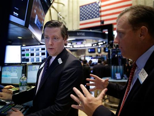 Traders work on the floor at the New York Stock Exchange in New York, Wednesday, July 8, 2015. Hong Kong's main stock index plummeted as much as 8.5 percent on Wednesday as a sell-off in mainland Chinese shares accelerated despite new measures to support the market; U.S. stocks were poised to open lower. (AP Photo/Seth Wenig)