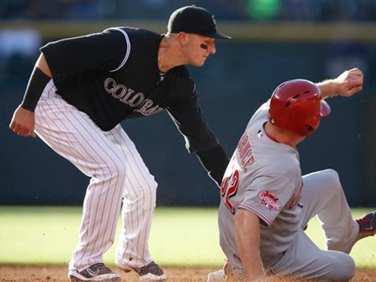 Colorado Rockies shortstop Troy Tulowitzki , left, tags out Cincinnati Reds' Jay Bruce as he tries to steal second base in the third inning of a baseball game Saturday, July 25, 2015, in Denver.