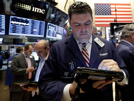 Trader Robert McQuade, center, works on the floor of the New York Stock Exchange, Tuesday, Aug. 18, 2015.