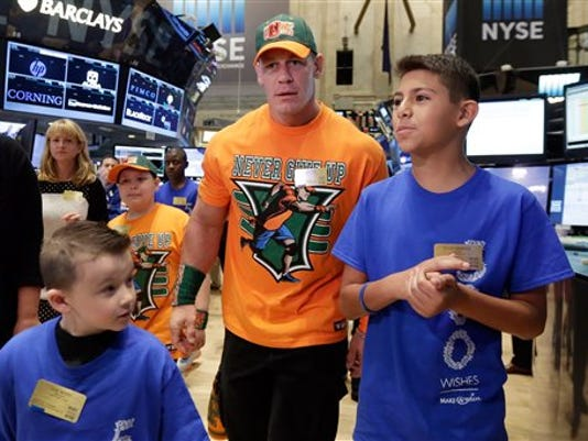 World Wrestling Entertainment superstar John Cena, center, is accompanied by Make-A-Wish participants Evan Maher, and Elijah Mendoza, foreground left and right, as he visits the trading floor, Friday, Aug. 21, 2015, before ringing the New York Stock Exchange opening bell. To date, WWE superstars and divas have granted more than 6,000 wishes. This was Cena's 500th granted wish. (AP Photo/Richard Drew)