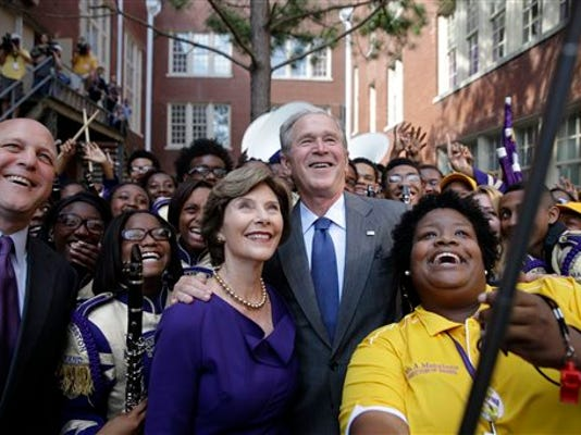 Former President George W. Bush poses for a 'selfie' photo with former first lady Laura Bush, marching band director Asia Muhaimin, right, and New Orleans Mayor Mitch Landrieu, far left, at Warren Easton Charter High School in New Orleans, Friday, Aug. 28, 2015. Bush is in town to commemorate the 10th anniversary of Hurricane Katrina, which is Saturday.