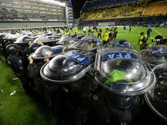 La policía eleva sus escudos para proteger a los jugadores de River Plate en el partido contra Boca Juniors por la Copa Libertadores, el jueves 14 de mayo de 2015. (AP Foto/Victor R. Caivano)