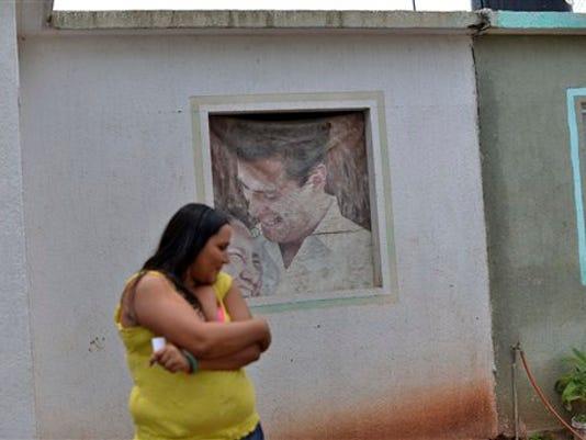 """En esta imagen del martes 21 de julio de 2015, Eliberta Díaz ante una casa abandonada donde se ha refugiado con sus dos hijas en Guamuchil, México. Pese a su origen humilde, Joaquín """"El Chapo"""" Guzmán no es apreciado entre las familias de granjeros pobres desplazadas por el cártel. Cientos de familias han abandonado la localidad montañosa de Sinaloa de Leyva en los últimos cinco años, movidos por el temor o las amenazas. (AP Foto/Fernando Brito)"""