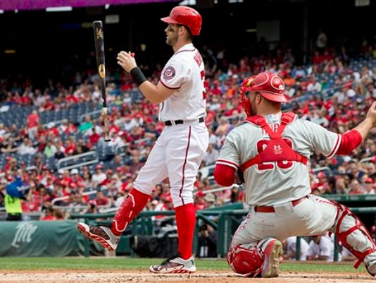 Washington's Bryce Harper (34) flips his bat in the air while batting in the first inning against the Philadelphia Phillies at Nationals Park in Washington on Sunday, next to Phillies catcher Erik Kratz (28). Harper was later involved in a dugout fight with teammate Jonathan Papelbon in the Nats' loss to the Phils.