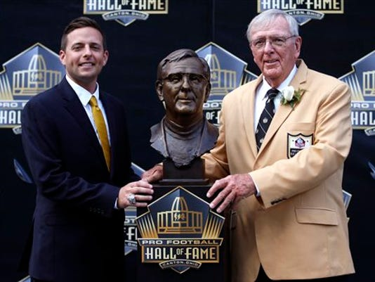 Former NFL contributor Ron Wolf, left, poses with a bust of himself and presenter, son, Eliot Wolf, during an induction ceremony at the Pro Football Hall of Fame,  Saturday, Aug. 8, 2015, in Canton, Ohio. (AP Photo/Gene J. Puskar)