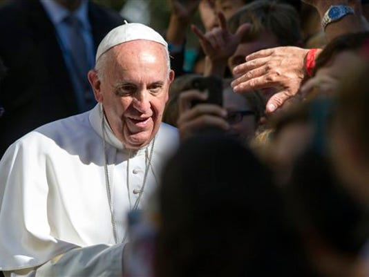 A man reaches out to touch Pope Francis as he prepares to depart the Apostolic Nunciature, the Vatican's diplomatic mission in the heart of Washington, en route to the Basilica of the National Shrine of the Immaculate Conception, Wednesday, Sept. 23, 2015. The Pope will celebrate Mass and will canonize Junipero Serra.