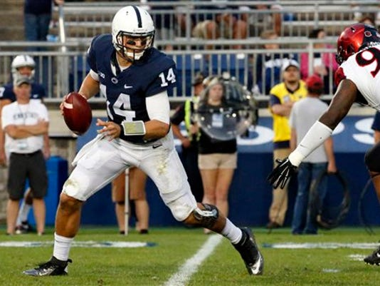 Penn State quarterback Christian Hackenberg (14) is forced out of the pocket by San Diego State defensive lineman Noble Hall (95) during the second half in State College on Saturday. Penn State won 37-21.