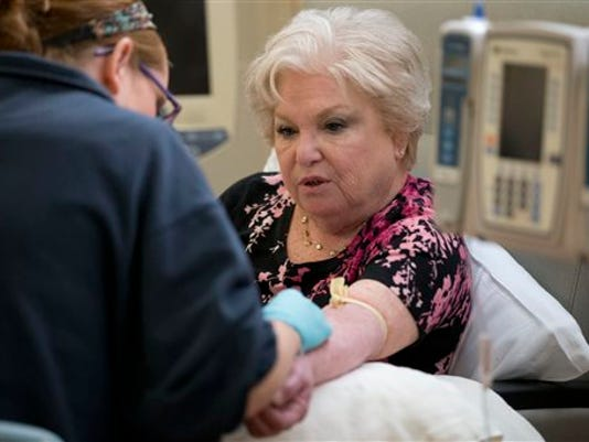 Nurse Caitlin Fanning, left, inserts an IV for Judith Bernstein's chemotherapy at the Fox Chase Cancer Center in Philadelphia on Tuesday, Aug. 4, 2015. Bernstein has had eight different types of cancer over the last two decades, all treated successfully.
