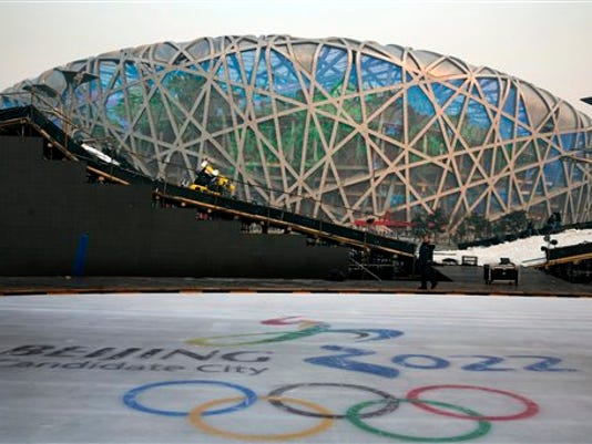 A worker walks past an ice rink with the logo for Beijing's Winter Olympics bid in December.