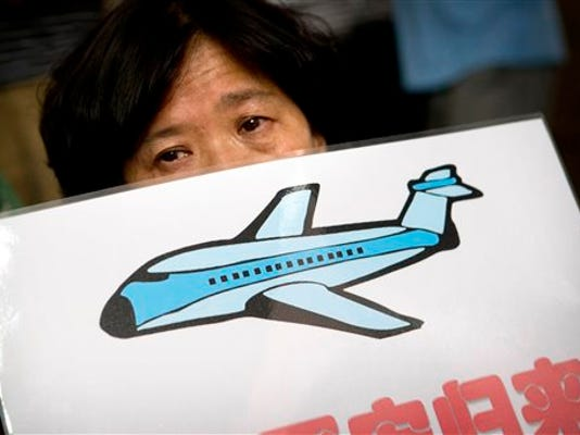 A family member of a passenger aboard Malaysia Airlines Flight 370 demonstrates outside the company's offices in Beijing, Thursday, Aug. 6, 2015. Families aching for closure after their relatives disappeared aboard Malaysia Airlines Flight 370 last year vented deep frustration Thursday at conflicting signals from Malaysia and France over whether the finding of a plane part had been confirmed.