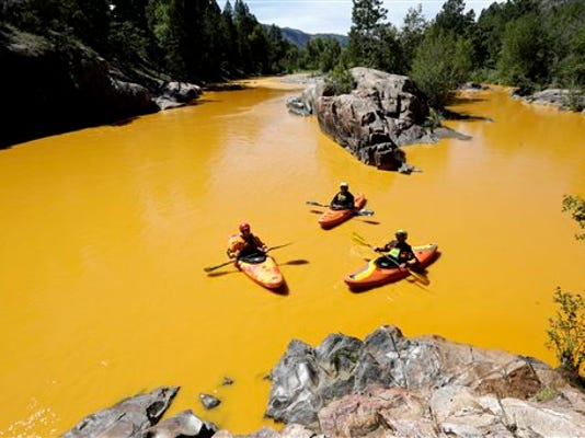 In this Thursday, Aug. 6, 2015 file photo, people kayak in the Animas River near Durango, Colo., in water colored yellow from a mine waste spill. A crew supervised by the U.S. Environmental Protection Agency has been blamed for causing the spill while attempting to clean up the area near the abandoned Gold King Mine.