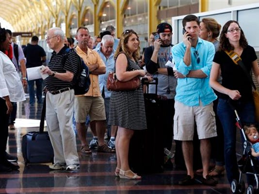 People stand in line at Washington's Reagan National Airport after technical issues at a Federal Aviation Administration center in Virginia caused delays on Saturday, Aug. 15, 2015.