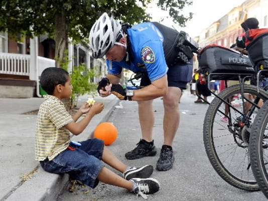 York City Police lieutenant Erik Kleynen, right, attaches a pin to a toy deputy badge given to him by Juan Andrew Martinez, 6, during National Night Out on  Aug. 4, 2015, in the 200 block of East College Street in York City.