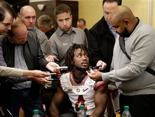FILE - In this Dec. 29, 2014, file photo, Florida State running back Dalvin Cook, center, is surrounded by reporters during the team's media day, for the Rose Bawl, in Los Angeles. The trial for suspended Florida State running back Dalvin Cook on charges that he punched a woman in the face outside a downtown bar has begun. The incident happened in June, and Cook's lawyer requested a speedy trial. It began Monday morning, Aug. 24, 2015, and is expected to last a day.