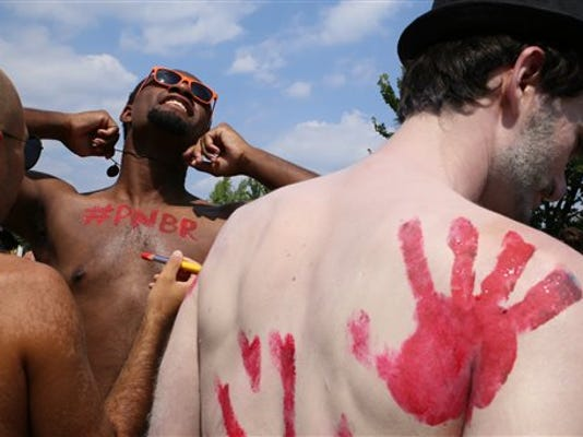 Participants in the Philly Naked Bike Ride paint each other before riding in Philadelphia on Saturday, Aug. 29, 2015. Thousands in various stages of undress have pedaled their way around the city to promote fuel conservation and positive body image.