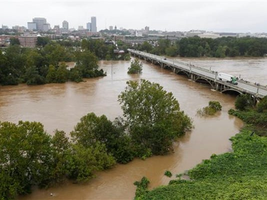 The Congaree River, swollen with floodwaters, flows under the Gervais Street bridge in West Columbia, S.C., Sunday, Oct. 4, 2015.