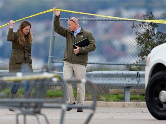 Luzerne County District Attorney Stefanie Salavantis, left, tours a crime scene with an investigator following reports of shots fired near a Wal-Mart store in Wilkes-Barre, Pa., Saturday, Oct. 17, 2015. Police in northeastern Pennsylvania have a suspect in custody.