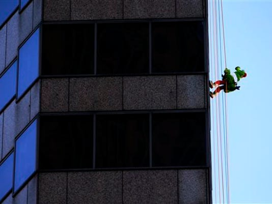 The Philadelphia Phillies' mascot, the Phillie Phanatic, rappels down a skyscraper as part of a annual fundraiser Friday, Oct. 23, 2015, in Philadelphia. The event was a fundraiser for the Philadelphia Outward Bound School, which offers outdoor programs aimed at building character and leadership skills.  (AP Photo/Matt Rourke)