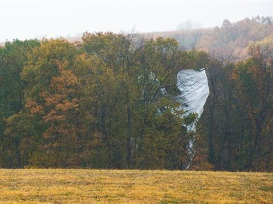 Part of what appears to be an unmanned Army surveillance blimp rests in the trees near Muncy, Pa., on Wednesday, Oct. 28, 2015. The 240-foot helium-filled unmanned Army surveillance blimp broke loose from its mooring in Maryland and floated over Pennsylvania for hours Wednesday with fighter jets on its tail, triggering blackouts across the countryside as it dragged its tether across power lines.