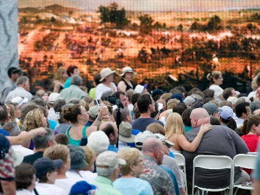 Against a backdrop of a battlefield scene, spectators listen to music from the U.S. Army Band during the official National Park Service commemoration of the 150th anniversary of the Battle of Gettysburg on June 30, 2013 in Gettysburg.