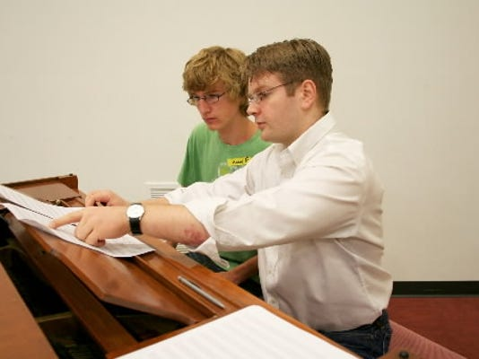 Chris Whittaker helps a piano student during a YSO summer camp session in July.