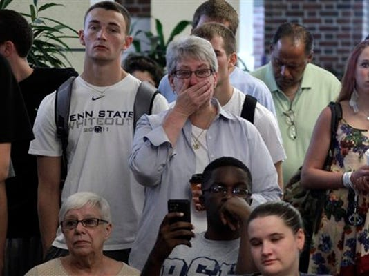 Susan DelPonte, center, of State College, reacts to a television in the HUB on the Penn State University main campus in State College, Pa., as the NCAA sanctions against the Penn State University football program are announced Monday, July 23, 2012.