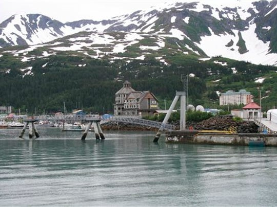 "FILE - This July 9, 2012 file photo shows the tiny community of Whittier, Alaska, where most of the 180 year-round residents live in the tall condo in the back, a former Army garrison. KTUU reports about 90 percent of the movie ""Hunter Killer"" will be filmed in Whittier. Whittier chamber officials said Friday, Dec. 12, 2014, that three months of pre-production will begin in January 2015, followed by three months of filming."