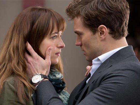 ", Dakota Johnson, left, and Jamie Dornan  in a scene from ""Fifty Shades of Grey."""